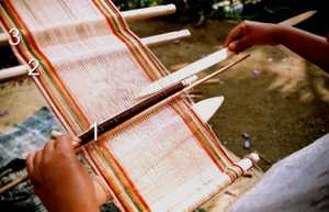 Using a shed stick when weaving rugs