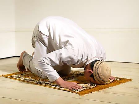 Muslim Man Praying on an Islamic Prayer Rug by Nazmiyal