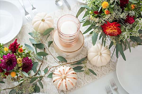 Mini pumpkins and Bright florals make a beautiful Thanksgiving table spread.