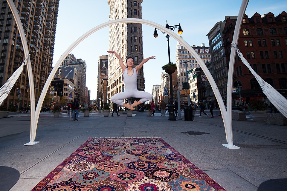 NYC antique rug photography project - A ballet dancer jumps and poses by Flatiron building NYC on top of Nazmiyal antique rugs