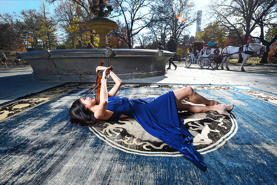 A violinist relaxes on top of a 19th century NingXia carpet from Nazmiyal Antique Rugs by a fountain in Central Park, NYC