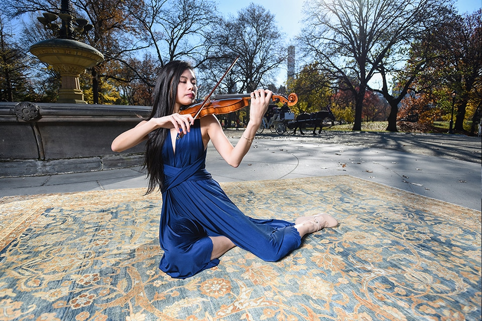 A Violinist Performs On Top Of An Antique Kerman Carpet By Nazmiyal Antique Rugs in Central Park NYC