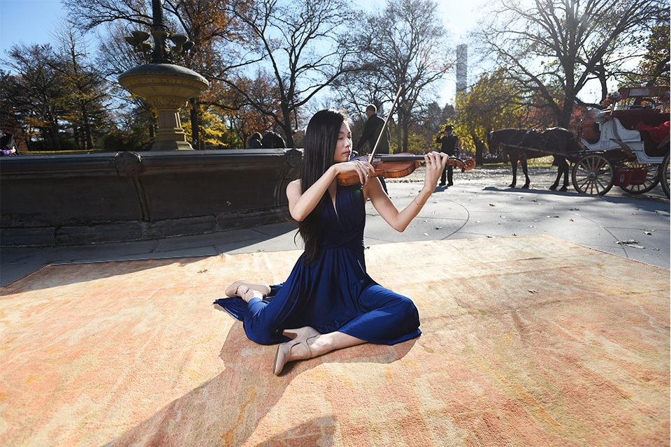 Violinist plays on an antique rug by a fountain in Central Park NYC