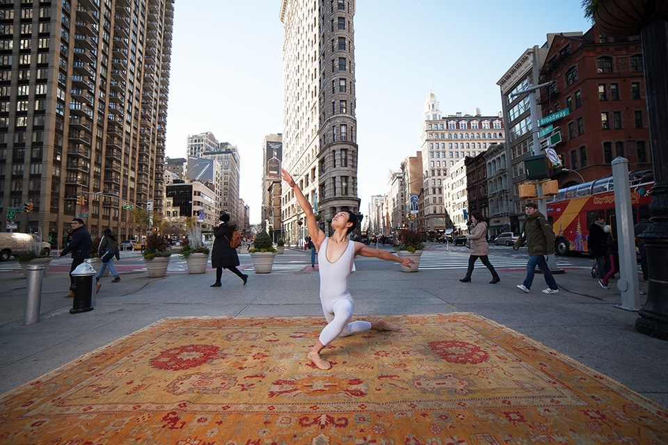 A ballet dancer poses on top of an antique Oushak rug from Nazmiyal Antique Rugs by the Flat Iron building NYC