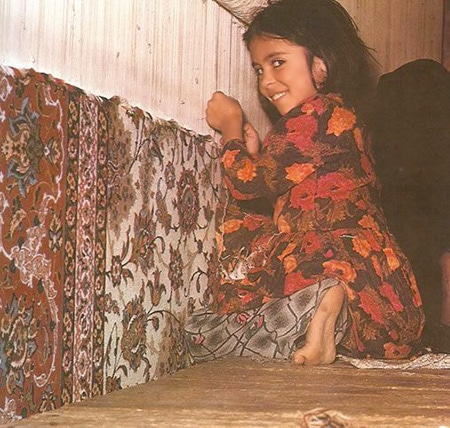 A Young Girl Weaving A Carpet on A Rug Loom by Nazmiyal